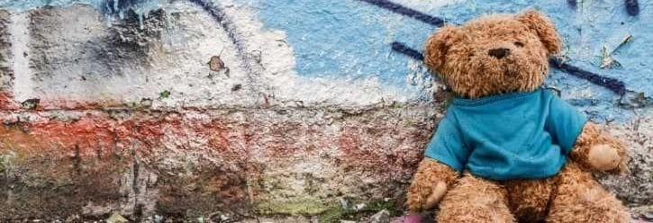 teddy bear leaning against a painted wall